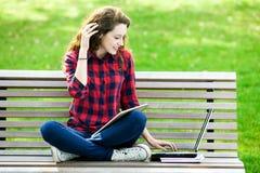 компьтер-книжка девушки стенда используя Стоковые Фотографии RF