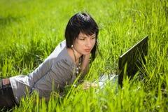компьтер-книжка девушки outdoors используя Стоковые Фото