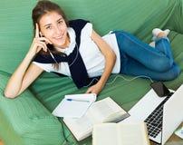 компьтер-книжка девушки домашняя используя детенышей Стоковая Фотография RF