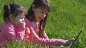компьтер-книжка детей outdoors Маленькие девочки на зеленой траве Сестры с компьтер-книжкой в парке Дети в розовых одеждах playin сток-видео