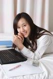 компьтер-книжка женщины кровати Стоковое фото RF