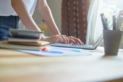 Компьтер-книжка женщины работая на деревянном столе в офисе в свете утра Стоковые Фото