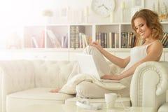 компьтер-книжка используя детенышей женщины Стоковая Фотография
