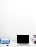 Компьтер-книжка и бумажный поднос на столе офиса Стоковые Фото