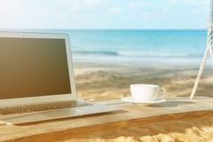 Компьтер-книжка и вид на море чашки кофе Стоковые Изображения RF