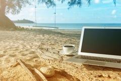 Компьтер-книжка и вид на море чашки кофе Стоковые Фотографии RF