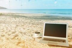 Компьтер-книжка и вид на море чашки кофе Стоковая Фотография