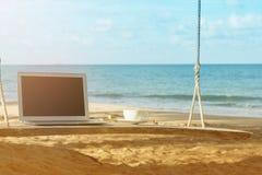Компьтер-книжка и вид на море чашки кофе Стоковые Изображения