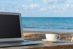 Компьтер-книжка и вид на море чашки кофе Стоковое Фото