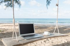 Компьтер-книжка и вид на море чашки кофе Стоковое Изображение