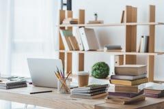 компьтер-книжка и воспитательные книги на таблице в свете Стоковые Фотографии RF