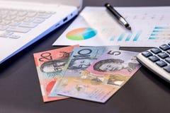 Компьтер-книжка и диаграмма доллара Aud на черноте стоковое изображение rf