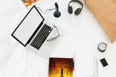 Компьтер-книжка или тетрадь пустого экрана с всеми вещами вокруг на кровати внутри Стоковое Изображение