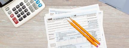 Компьтер-книжка и калькулятор на форме 2015 IRS 1040 Стоковая Фотография