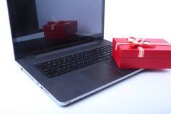 Компьтер-книжка и коробка подарков рождества на белом столе Стоковые Фотографии RF