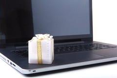 Компьтер-книжка и коробка подарков рождества на белом столе Стоковые Изображения RF