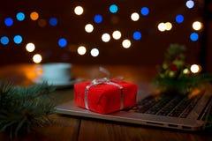 Компьтер-книжка и красная подарочная коробка на деревянной таблице с светами рождества Стоковое Изображение