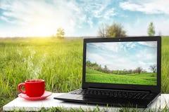 Компьтер-книжка и чашка горячего кофе на природе предпосылки живописной Стоковая Фотография RF