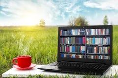 Компьтер-книжка и чашка горячего кофе на природе предпосылки живописной, внешнего офиса Концепция библиотеки EBook Магазин книг и стоковые изображения