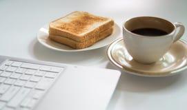 Компьтер-книжка и чашка кофе с здравицей Стоковые Изображения