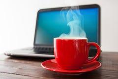 Компьтер-книжка и чашка кофе стоковое фото