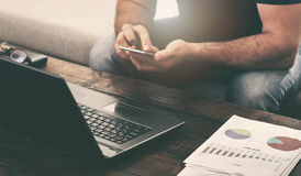 Компьтер-книжка и smartphone бизнесмена работая на софе дома Стоковые Фото