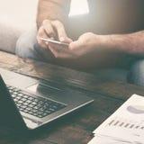Компьтер-книжка и smartphone бизнесмена работая на софе дома Стоковое фото RF