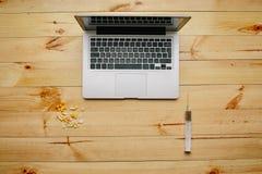 Компьтер-книжка и smartphone с медицинами на деревянном столе Стоковые Изображения