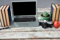Компьтер-книжка, камера и книги на таблице Стоковое Фото