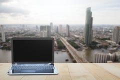Компьтер-книжка компьютера на верхней части деревянного стола на запачканной предпосылке города Стоковое Фото