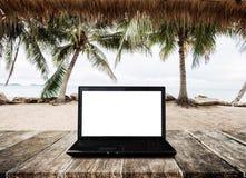 Компьтер-книжка компьютера на деревянном столе, на пляже в лете Экран компьютера пути клиппирования стоковая фотография rf