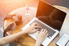 Компьтер-книжка компьютера пользы женщины рук в ресторане Стоковая Фотография