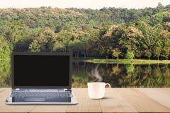 Компьтер-книжка компьютера с черным экраном и горячей кофейной чашкой на верхней части деревянного стола на предпосылке озера и л Стоковое Фото