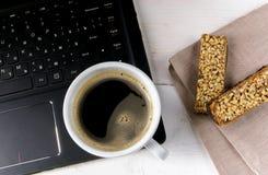 Компьтер-книжка, кофе и светлая закуска с помадками Стоковые Фото