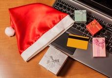 Компьтер-книжка, кредитная карточка, подарочные коробки и взгляд сверху шляпы santa Стоковая Фотография