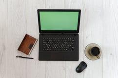 Компьтер-книжка, кружка кофе и тетрадь на предпосылке деревянного стола Взгляд сверху Стоковая Фотография