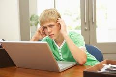 компьтер-книжка мальчика домашняя смотря подростков используя потревожено стоковые фото