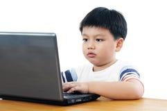 компьтер-книжка мальчика используя детенышей Стоковая Фотография RF