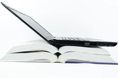 Компьтер-книжка над книгами Стоковые Изображения