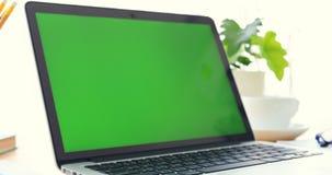 Компьтер-книжка на столе с зеленым экраном видеоматериал