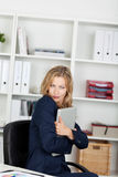 Компьтер-книжка обнимать коммерсантки в офисе Стоковые Изображения