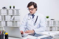 компьтер-книжка доктора используя Стоковые Изображения