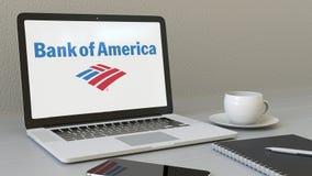 Компьтер-книжка отверстия с логотипом Государственного банка Америки на экране Зажим передовицы 4K современного рабочего места сх иллюстрация штока