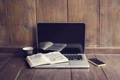 Компьтер-книжка, открытая кружка книги, сотового телефона и кофе Стоковая Фотография