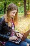 Компьтер-книжка пользы девушки битника в парке Стоковое фото RF