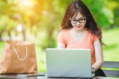 Компьтер-книжка пользы девушки в парке Стоковые Изображения RF