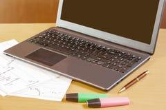 Компьтер-книжка, ручка и highlighters на столе офиса Стоковое фото RF
