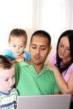 компьтер-книжка семьи используя детенышей Стоковое Фото