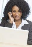 Компьтер-книжка сотового телефона коммерсантки женщины афроамериканца Стоковая Фотография RF