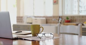 Компьтер-книжка с кружкой документов, зрелища и кофе на таблице 4k акции видеоматериалы